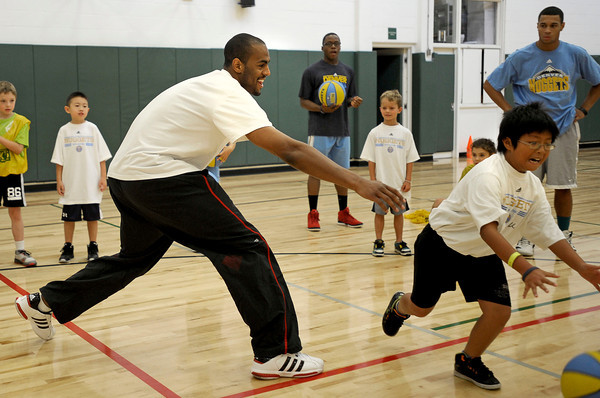 "Arron Afflalo, an NBA player of the Denver Nuggets, goes to tag Kevin Xu, 10, of Boulder, during a dribbling exercise in South Boulder Rec Center. Afflalo came to visit a kids basketball camp Tuesday morning to sign autographs, play and talk with the kids. August 7, 2012. Rachel Woolf/ For the Daily Camera. For more photos, go to  <a href=""http://www.dailycamera.com"">http://www.dailycamera.com</a>."