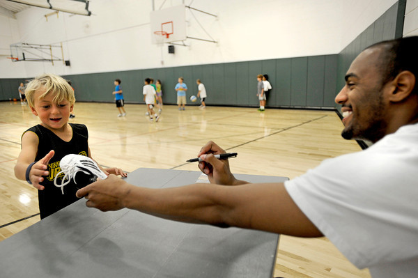 "From left, Arron Afflalo, an NBA player of the Denver Nuggets, hands Owen Reid, 7, of Louisville, his newly autographed shoe with at South Boulder Rec. Center. Afflalo came to visit a kids basketball camp Tuesday morning to sign autographs, play and talk with the kids. August 7, 2012. Rachel Woolf/ For the Daily Camera. For more photos, go to  <a href=""http://www.dailycamera.com"">http://www.dailycamera.com</a>."
