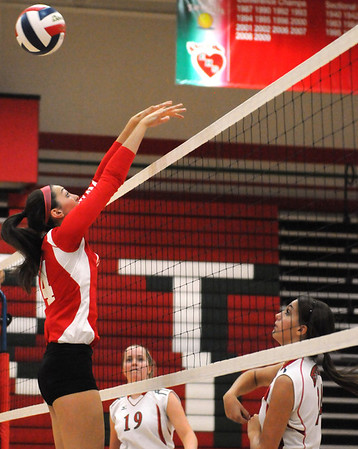 Effingham's Brittany Beals (left, 14, red), goes for a block on a spike by Shelby Nunamaker (right, 24, white) while teammate Katie Tegeler (center, 19, white) looks on during Meet the Hearts night.