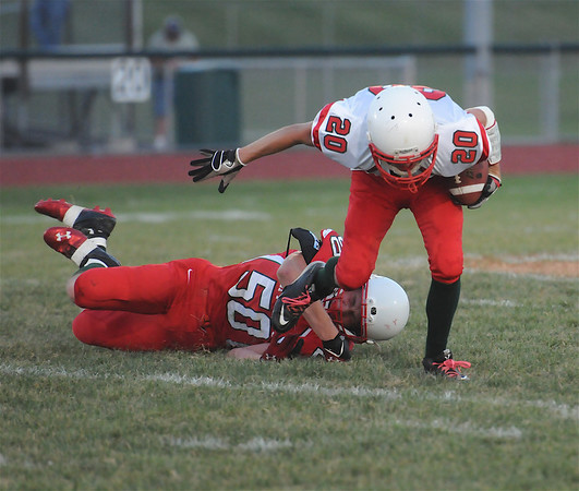 Effingham's Tyler Myers (20) fights loose from a tackle by fellow Effingham player Brandon Loy (50) during the annual Buck Bowl scrimmage at Klosterman Field.