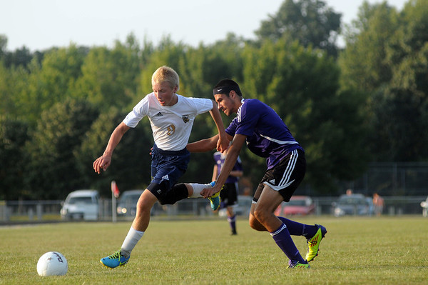 Teutopolis' Justin Deters fights off contact from a Taylorville defender during the Wooden Shoes' season opener.