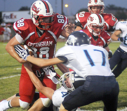 Effingham's Carter Hayes (88) fights through contact from an unidentified Breese Mater Dei player and Austin Timmermann (17)at Klosterman Field.