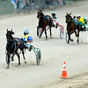 Michael Cox, riding Smokin Moni, looks back at his competition, Gorgeous Dune (left) and Heartland Desire (right) during the Topline 2-Year-Old Pace race at the Effingham County Fair's harness racing.