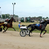 Incredible Filly, driven by Michael Cox, leads Queen Beatrice, driven by Darla Martin, coming around a turn during the Topline 3-Year-Old and Up Pace Division 2 race at the Effingham County Fair's harness racing.