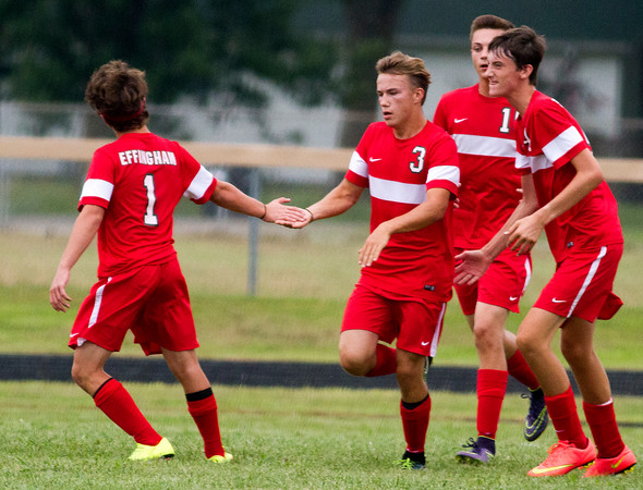 Effingham's Danny Hortenstine (3) receives praise from his teammates after converting on a penalty kick in the first half of a match against Altamont.