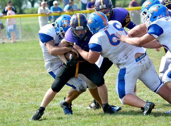 Newton's Bryce Hance (34, left) and Wyatt Emmerich (69, right) tackle Georgetown-Ridge Farm's Landon Noggle as Hance attempts to strip the ball in Georgetown.