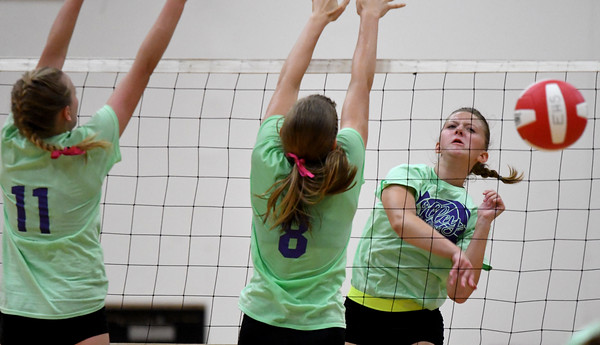 Effingham's Chloe Martin spikes the ball past St. Anthony's Hannah Will (11) and Meg Richards (8) during the Volley for a Cure matchup at Effingham High School.<br /> Chet Piotrowski Jr./Piotrowski Studios