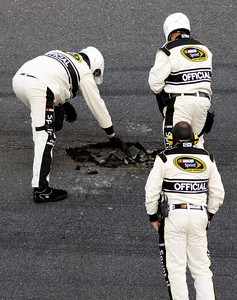 NASCAR officials examine broken asphalt in the track during the second red flag delay in the NASCAR Daytona 500 auto race at Daytona International Speedway in Daytona Beach, Fla., Sunday, Feb. 14, 2010. (AP Photo/Bill Friel)