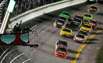 Jamie McMurray, front, takes the checkered flag ahead of Dale Earnhardt Jr. to win the NASCAR Daytona 500 auto race at Daytona International Speedway in Daytona Beach, Fla., Sunday, Feb. 14, 2010. (AP Photo/David Graham)