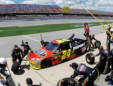 Crew members work to refuel and change the tires on Jeff Gordon's car during the N ASCAR Sprint Cup Series Aaron's 499 auto race at Talladega Superspeedway in Talladega, Ala., Sunday, April 25, 2010. (AP Photo/Rainier Ehrhardt)
