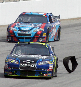 A piece of tire flies off Mark Martin's car, foreground, during the NASCAR Sprint Cup Series Kobalt Tools 500 auto race at Atlanta Motor Speedway in Hampton, Ga., Sunday, March 7, 2010. (AP Photo/Glenn Smith)
