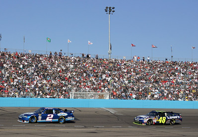 Kurt Busch (2) leads Jimmie Johnson (24) through Turn 4 during the NASCAR Checker O'Reilly Auto Parts 500 auto race at Phoenix International Raceway in Avondale, Ariz., Sunday, Nov. 15, 2009. (AP Photo/Mary Schwalm)