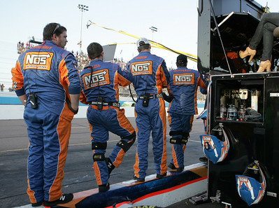 The pit crew for Kyle Busch looks on as they stand on the pit wall as Busch falls out of place to win the championship during the NASCAR Nationwide Series Able Body Labor 200 auto race at Phoenix International Raceway in Avondale, Ariz., Saturday, Nov. 14, 2009. (AP Photo/Mary Schwalm)