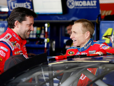 Driver Tony Stewart, left, and Mark Martin talk in the garage during a rain delay during practice for Sunday's NASCAR Sprint Cup Checker O'Reilly Auto Parts 500 auto race at Phoenix International Raceway in Avondale, Ariz., Saturday, Nov. 14, 2009. (AP Photo/Mary Schwalm)