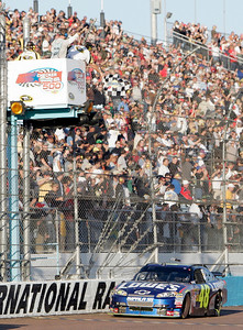 Jimmie Johnson takes the checkered flag to win the NASCAR Sprint Cup Series' Checker O'Reilly Auto Parts 500 auto race at Phoenix International Raceway in Avondale, Ariz., Sunday, Nov. 15, 2009. (AP Photo/Jason Babyak)