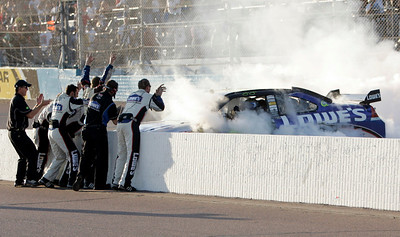 Jimmie Johnson's crew cheers him on as he does a burnout the straightaway after winning the NASCAR Sprint Cup Series' Checker O'Reilly Auto Parts 500 race at Phoenix International Raceway in Avondale, Ariz., Sunday, Nov. 15, 2009. (AP Photo/Jason Babyak)