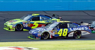 Mark Martin (5) and Jimmie Johnson (48) race side-by-side during the NASCAR Checker O'Reilly Auto Parts 500 race at Phoenix International Raceway in Avondale, Ariz., Sunday, Nov. 15, 2009. (AP Photo/Mary Schwalm)