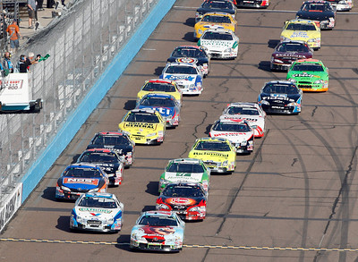 Cars led by pole sitter Denny Hamlin, front right, take the green flag at the start during the NASCAR Nationwide Series Able Body Labor 200 auto race at Phoenix International Raceway in Avondale, Ariz., Saturday, Nov. 14, 2009. (AP Photo/Mary Schwalm)