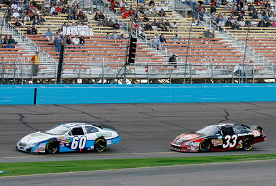 Carl Edwards (60) leads Kevin Harvick (33) out of Turn 1 after a restart during the NASCAR Nationwide Series Able Body Labor 200 auto race at Phoenix International Raceway in Avondale, Ariz., Saturday, Nov. 14, 2009. Edwards won the race, Harvick was second. (AP Photo/Mary Schwalm)