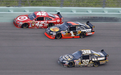 Juan Pablo Montoya (42), of Colombia, slides along the wall during the NASCAR Sprint Cup series auto race at Homestead-Miami Speedway in Homestead, Fla., Sunday, Nov. 22, 2009. Also shown are Martin Truex Jr. (1) and Ryan Newman (239). (AP Photo/Lynne Sladky)