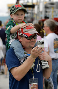 ** CORRECTS SPELLING OF BRADENTON ** Jim Adams III, bottom, of Bradenton, Fla., takes a photo as his son Jayden, 19 months, looks on before the NASCAR Ford 400 Sprint Cup series auto race at the Homestead-Miami Speedway in Homestead, Fla., Sunday, Nov. 22, 2009. (AP Photo/Lynne Sladky)
