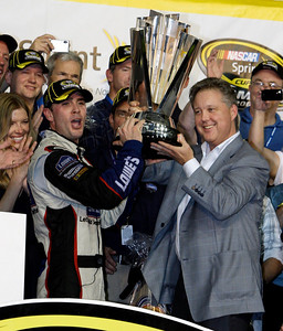 Jimmie Johnson, left, raises the trophy with NASCAR chairman Brian France, right, after winning the NASCAR Sprint Cup Series season championship at Homestead-Miami Speedway in Homestead, Fla., Sunday, Nov. 22, 2009. (AP Photo/Chuck Burton)