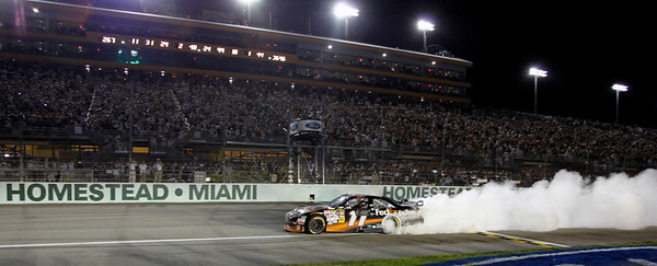 Denny Hamlin does a burnout after winning the NASCAR Sprint Cup Series' Ford 400 auto race at Homestead-Miami Speedway in Homestead, Fla., Sunday, Nov. 22, 2009. (AP Photo/Terry Renna)
