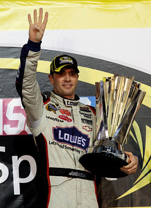 Jimmie Johnson celebrates after winning his fourth consecutive NASCAR Sprint Cup Series season title, at Homestead-Miami Speedway in Homestead, Fla., Sunday, Nov. 22, 2009. (AP Photo/Terry Renna)