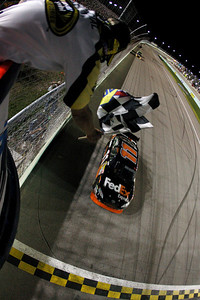 Denny Hamlin (11) crosses the finish line to win the NASCAR Sprint Cup Series' Ford 400 auto race at Homestead-Miami Speedway on Sunday, Nov. 22, 2009, in Homestead, Florida. (AP Photo/Chris Graythen, Pool)