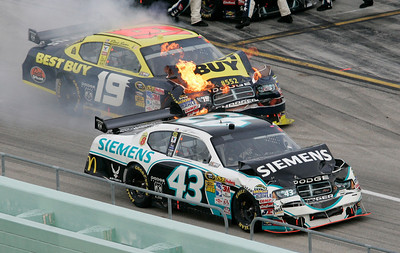 Flames come from under the hood of Elliott Sadler's car on pit row during the NASCAR Sprint Cup Series auto race in Homestead, Fla., Sunday, Nov. 22, 2009. Also shown is Reed Sorenson (43). (AP Photo/David Graham)
