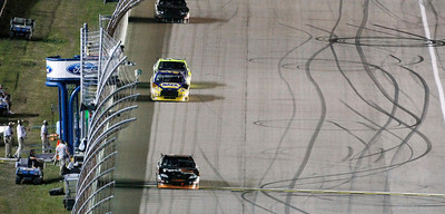 Denny Hamlin takes the checkered flag, winning the NASCAR Sprint Cup Series' Ford 400 auto race at Homestead-Miami Speedway in Homestead, Fla., Sunday, Nov. 22, 2009. (AP Photo/J Pat Carter)