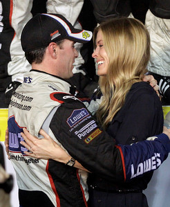 Jimmie Johnson, left, is congratulated by his wife, Chandra, right, after winning the NASCAR Sprint Cup Series season championship at Homestead-Miami Speedway in Homestead, Fla., Sunday, Nov. 22, 2009. (AP Photo/Terry Renna)
