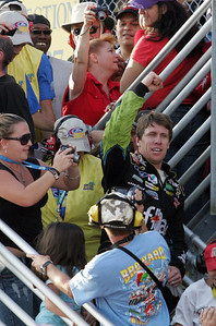 NASCAR driver Carl Edwards raises his fist after running into the stands following his win of  the Ford 400 auto race, Sunday Nov. 21, 2010, in Homestead, Fla. (AP Photo/Jim Topper)