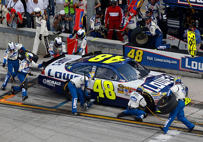 The pit crew for the No. 48 Lowe's Chevrolet driven by Jimmie Johnson, rush to the car during a pit stop during the Ford 400 auto race, Sunday, Nov. 21, 2010, at Homestead-Miami Speedway in Homestead, Fla. (AP Photo/Wilfredo Lee)