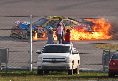 Fans watch as the No. 18 M&M's Toyota being driven by Kyle Busch bursts into flames during the Ford 400 auto race, Sunday, Nov. 21, 2010, at Homestead-Miami Speedway in Homestead, Fla. (AP Photo/Wilfredo Lee)