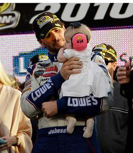 NASCAR driver Jimmie Johnson holds his daugher, Geneviene, after winning his fifth Sprint Cup Series Championship Sunday, Nov. 21, 2010 in Homestead, Fla.(AP Photo/Terry Renna)