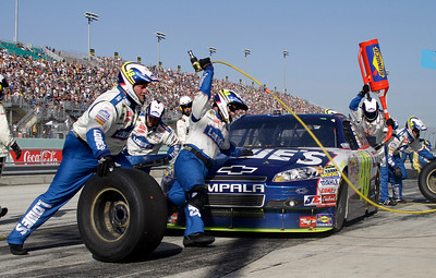 NASCAR driver Jimmie Johnson's pit crew work on the car during a pit stop at the Ford 400 auto race, Sunday Nov. 21, 2010 in Homestead, Fla. (AP Photo/Terry Renna)