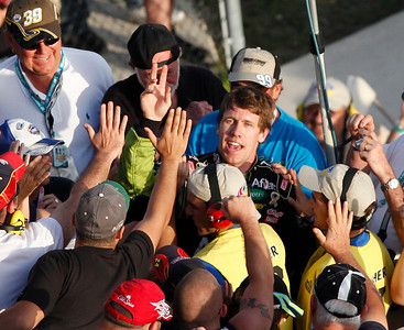 NASCAR driver Carl Edwards, center, high fives fans after winning the Ford 400 auto race, Sunday, Nov. 21, 2010, at Homestead-Miami Speedway in Homestead, Fla. (AP Photo/Wilfredo Lee)