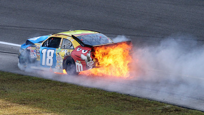 The no. 18 M&M Toyota driven by NASCAR driver Kyle Bush burst into flames after hitting the wall during the Ford 400 auto race Sunday Nov. 21, 2010 in Homestead, Fla. (AP Photo/David Graham)
