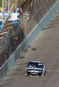 Carl Edwards takes the checkered flag to win the Ford 400 auto race Sunday Nov. 21, 2010 in Homestead, Fla. (AP Photo/David Graham)