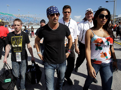 Musician Bret Michaels, center, arrives with his entourage before the start of the Ford 400 auto race on Sunday, Nov. 21, 2010, in Homestead, Fla. (AP Photo/Lynne Sladky)
