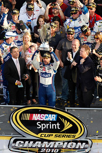 NASCAR driver Jimmie Johnson, center, holds up his trophy after winning the NASCAR Sprint Cup Series Championship, Sunday, Nov. 21, 2010, at Homestead-Miami Speedway in Homestead, Fla. (AP Photo/Wilfredo Lee)