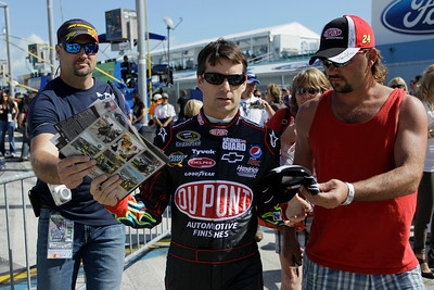 NASCAR driver Jeff Gordon, center, signs autographs far fans Sunday, Nov. 21, 2010, in Homestead, Fla., before the start of the Ford 400 auto race. (AP Photo/J Pat Carter)