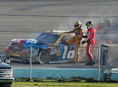 Kyle Busch is helped out of the No. 18 M&M's Toyota after it burst into flames during the Ford 400 auto race, Sunday, Nov. 21, 2010, at Homestead-Miami Speedway in Homestead, Fla. (AP Photo/Wilfredo Lee)