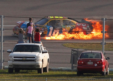 Fans watch as the No. 18 M&M's Toyota, driven by Kyle Busch, bursts into flames during the Ford 400 auto race, Sunday, Nov. 21, 2010, at Homestead-Miami Speedway in Homestead, Fla. (AP Photo/Wilfredo Lee)