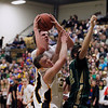 Record-Eagle/Jan-Michael Stump<br /> Traverse City Central center Tanner Kenney (40) and guard TJ Schepperly (32) fight for a rebound with Traverse City West forward Kendrick Meyer (32) in the third quarter of Thursday's game.