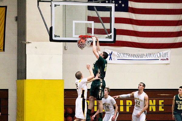 Record-Eagle/Jan-Michael Stump<br /> Traverse City West forward Trevor Commissaris (24) dunks on a trio of Traverse City Central players at the start of Thursday's game