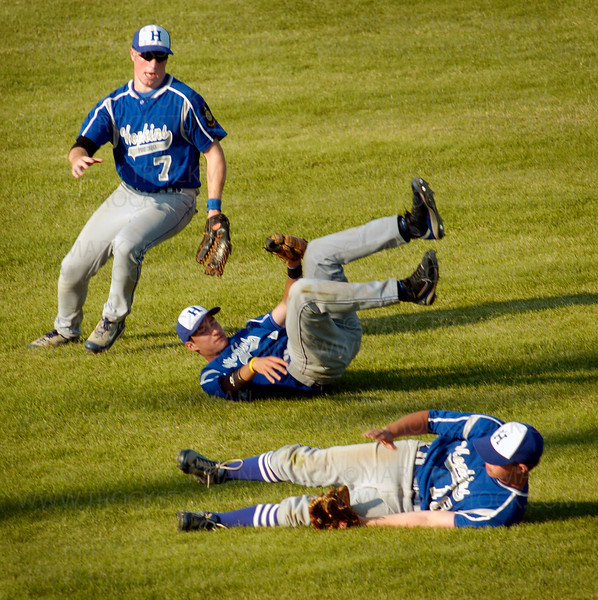Hopkins players lay strewn about the outfield after trying to catch a short fly ball hit by an Excelsior batter in the fourth inning Tuesday, June 17 in Minnetonka.  Hopkins lost to Excelsior 15-7.