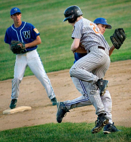 St. Louis Park's Matt Scudder slams into Wayzata's 2nd baseman, trying to knock the ball from his glove.  Wayzata trounced St. Louis Park 13-0 Wednesday, July 2 at Dakota Fields.