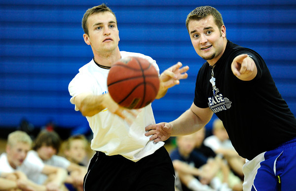 "Camp coach and BHS player Parker Ericson left, demonstrates passing strategy as Coach Matt Keefe describes the technique during basketball camp at Broomfield High School on Monday June 4, 2012<br /> For more photos go to  <a href=""http://www.broomfieldenterprise.com"">http://www.broomfieldenterprise.com</a> <br /> Photos by Paul Aiken<br /> <br /> BROOMFIELD HIGH BASKETBALL CAMP"